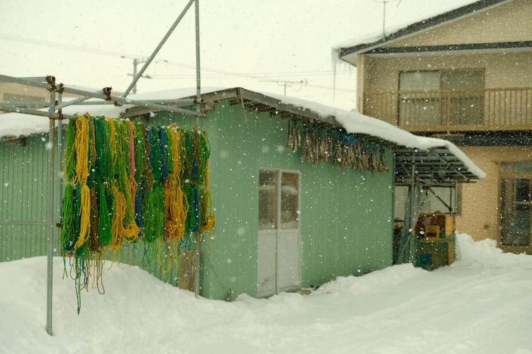 Snow covered houses by building during winter