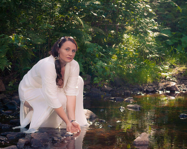 Portrait of mature woman with hands cupped in pond