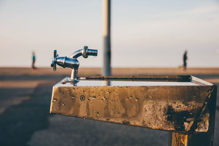 Close-Up Of Faucet By Road Against Sky