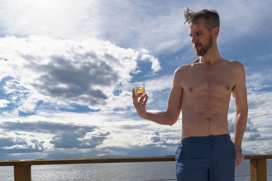 Landscape man on deck with drink Adult Beach Beverage Bourbon Caucasian Deck Drinking Glass Golden Handsome Holding Male Man Model Ocean Rocks Scotch Sea Shirtless Shorts Summer Swimsuit View Wearing Whiskey