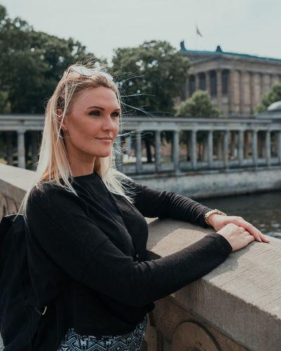 Portrait of smiling young woman against built structure