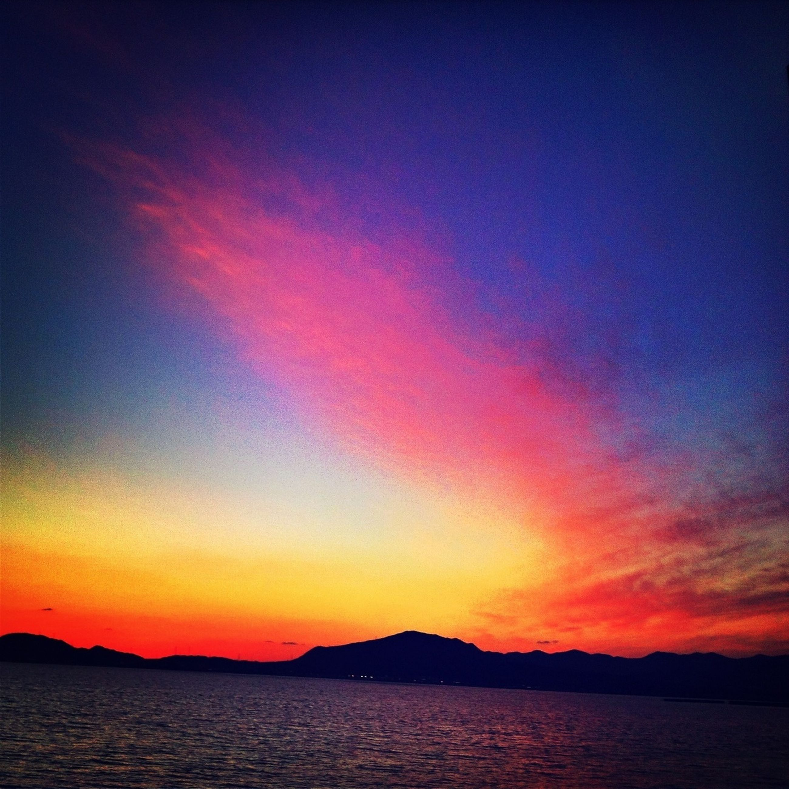 sunset, scenics, water, tranquil scene, tranquility, orange color, beauty in nature, waterfront, mountain, silhouette, sky, sea, idyllic, nature, mountain range, dusk, lake, majestic, dramatic sky, outdoors