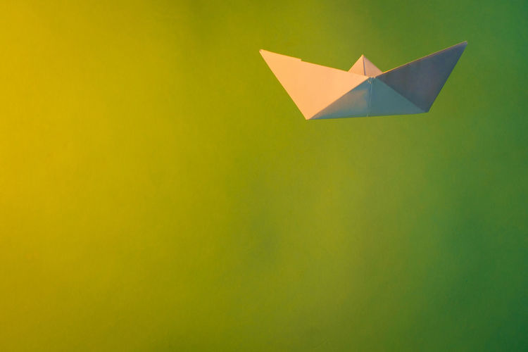 Close-up of paper boat with smoke against green background
