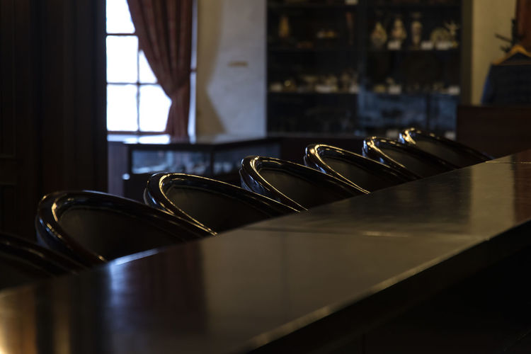 Row Of Black Chairs At Counter In Bar