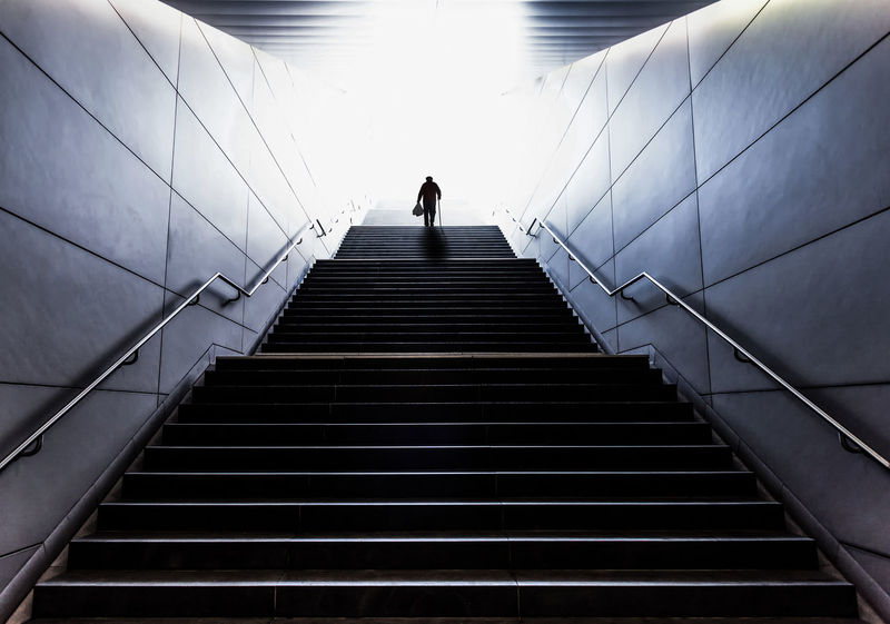 Light Silhouette Age Architecture Built Structure Diminishing Perspective Full Length Low Angle View Men Mobility Moving Up One Person Railing Real People Rear View Senior Senior Adult Staircase Steps And Staircases Stressful The Way Forward Walking Walking Cane