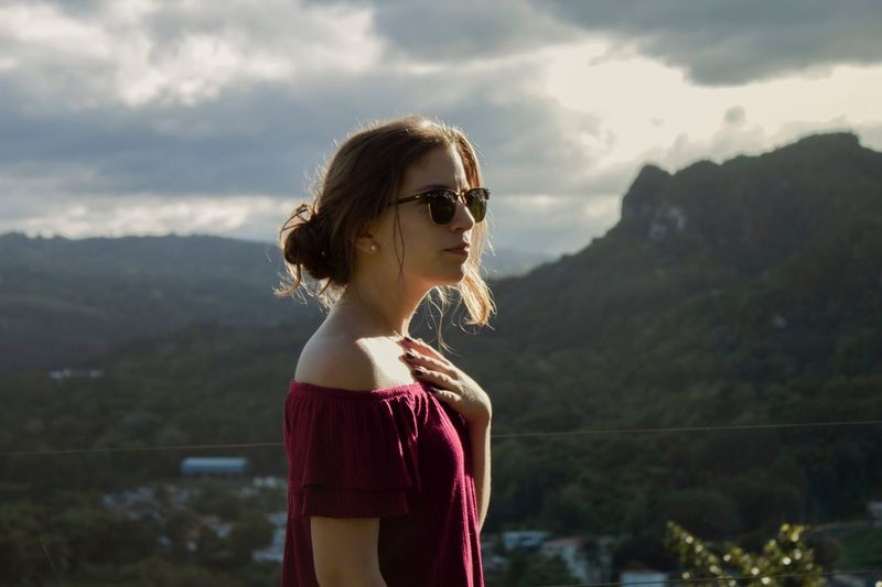 Side view of thoughtful woman standing against mountain