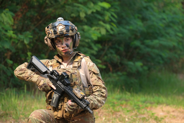 Young soldier holding gun outdoors