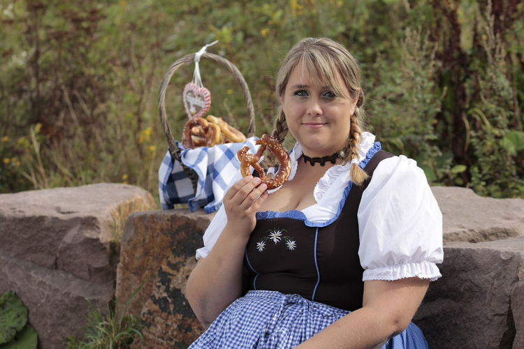Portrait of overweight young woman holding pretzel bread