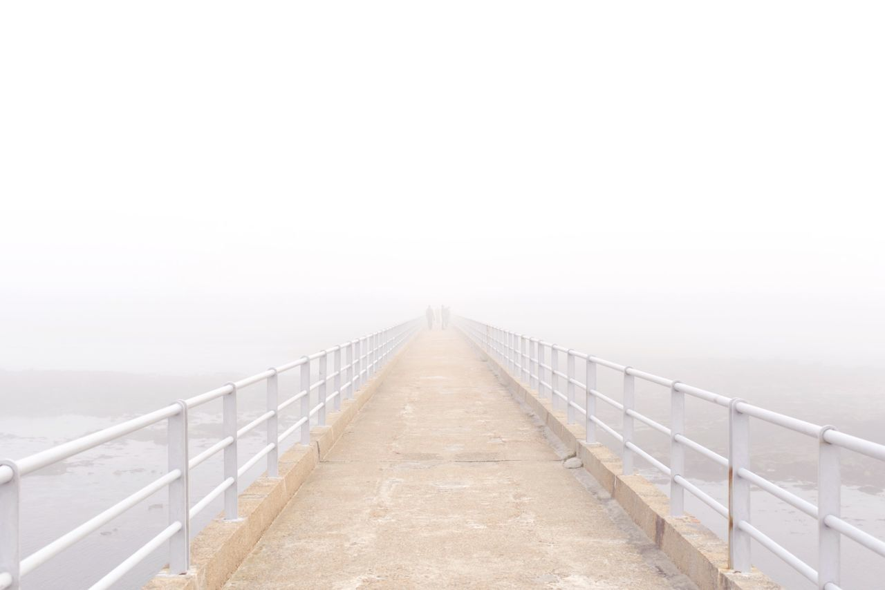 Footbridge over water in foggy weather