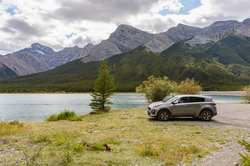 Car by lake against mountains
