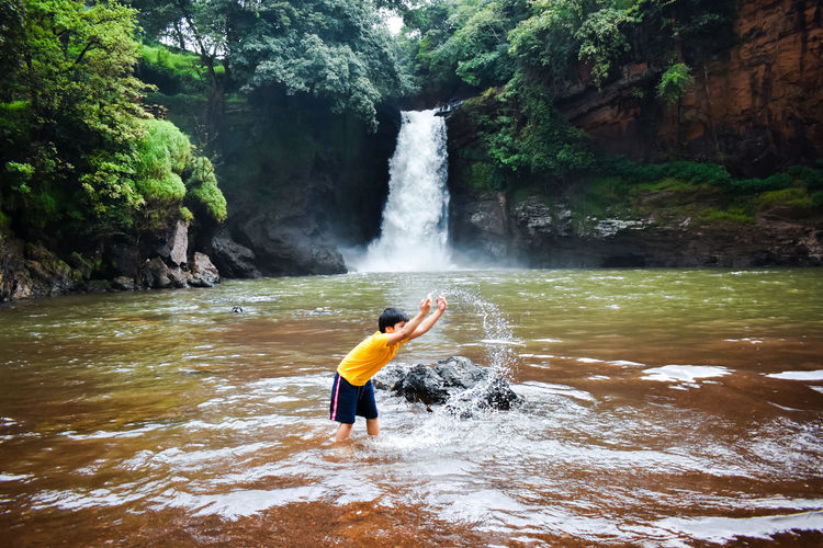 Boy surfing on rock in waterfall