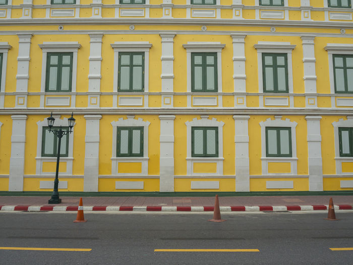 View of yellow building by road