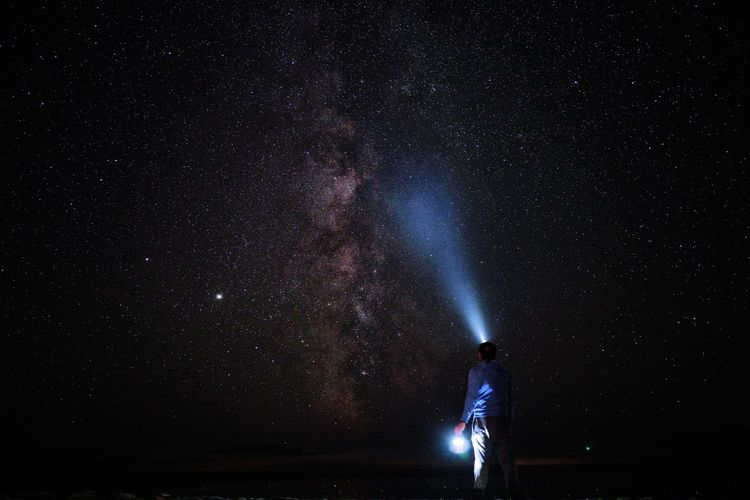 Full length of man standing against star field at night
