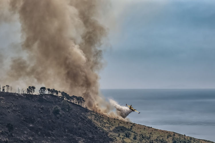 Airplane fighting forest fire against blue sky and sea