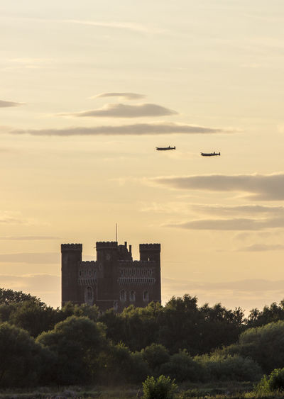 Airplanes flying over castle against sky