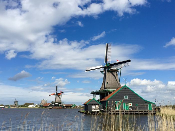 Windmills by river against cloudy sky