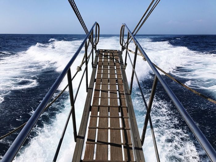 Sea waves splashing on railing against clear sky