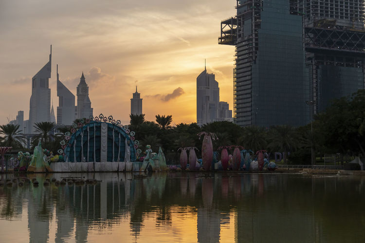 Reflection of buildings in city at sunset