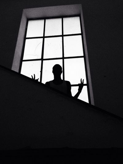 Silhouette person showing victory sign against window