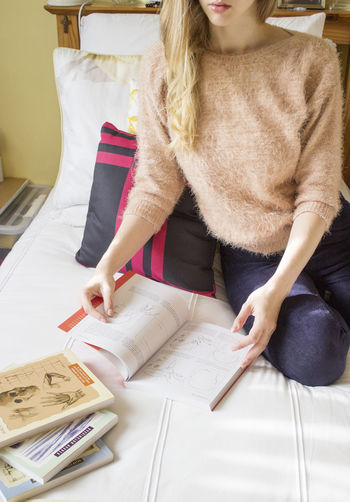 High angle view of woman reading book on bed