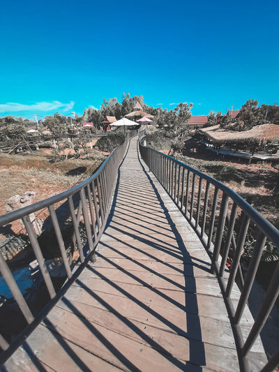 Footbridge against clear blue sky