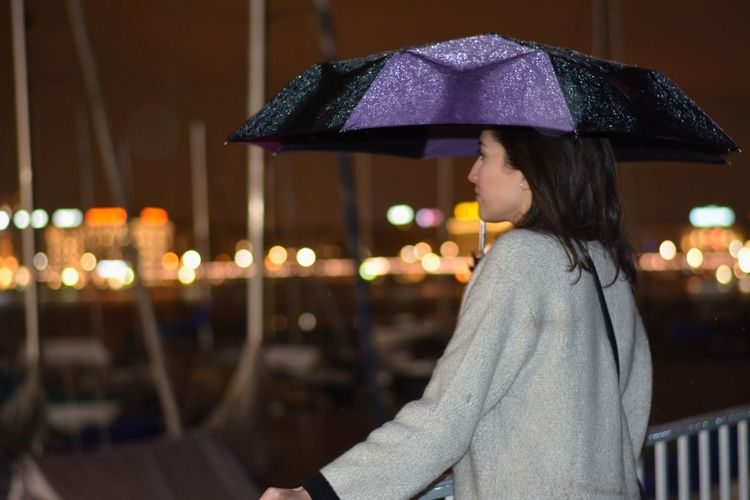 Side View Of Woman Holding Umbrella While Standing By Railing At Night