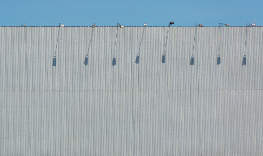 Low angle view of birds perching on wall against blue sky