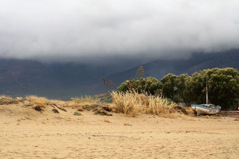 Abandoned boat on landscape against clouds