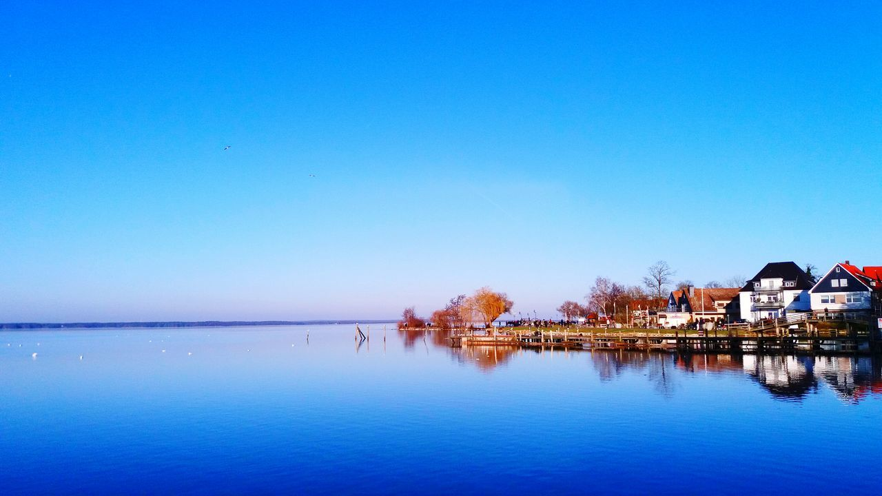 water, blue, built structure, copy space, clear sky, reflection, architecture, tranquil scene, building exterior, sea, tranquility, waterfront, outdoors, scenics, beauty in nature, nature, no people, sky, day