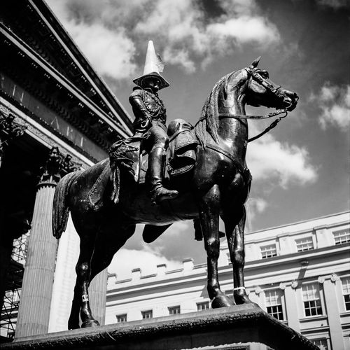 Glasgow's Duke of Wellington statue rocks a traffic cone outside of the Gallery of Modern Art. Duke Of Wellington Statue Glasgow  Quality Time Royal Exchange Square Scotland Tradition Travel Architecture Art And Craft Black And White Building Exterior Built Structure Cloud - Sky Creativity Day History Horse Human Representation Low Angle View No People Outdoors Sculpture Sky Statue Traffic Cone