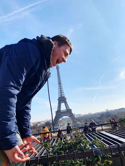 Optical illusion of man eating eiffel tower against sky in city