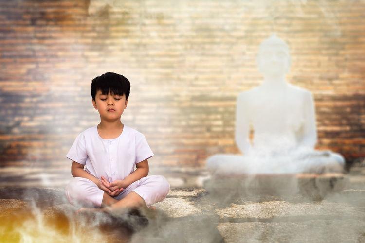 Boy sitting on cross