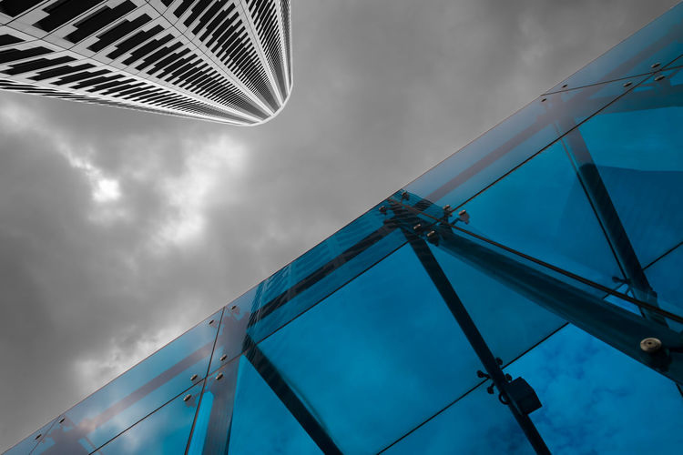 Look-up view of a modern office tower and a blue glass building under cloudy sky. Shine Architecture Blue Building Exterior Buildings City Cloud - Sky Clouds Design Diagonal Lines Glass Look-up Low Angle View Office Towers Sky