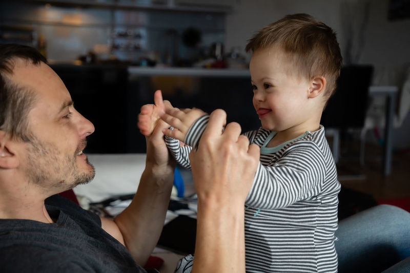 Babyboy Adult Bonding Boys Casual Clothing Child Childhood Cute Down Syndrome Family Family With One Child Holding Indoors  Innocence Lifestyles Males  Men Mental Health  Parent Playing Real People Side View Son Togetherness