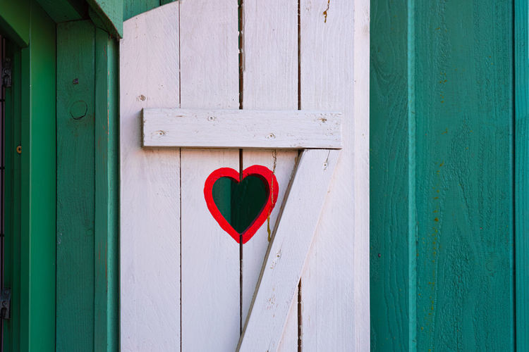 Red heart shape on blue door