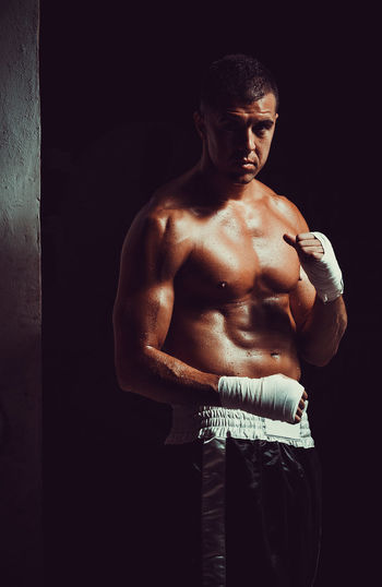 Portrait of shirtless male athlete wearing hand wrap while standing in darkroom
