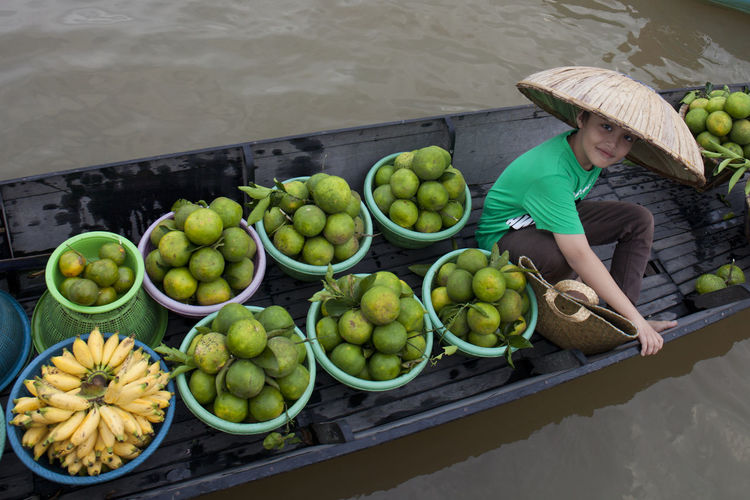 High angle portrait of boy in boat at floating market
