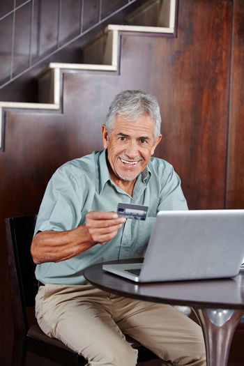 Portrait of smiling man shopping through credit card on laptop at home