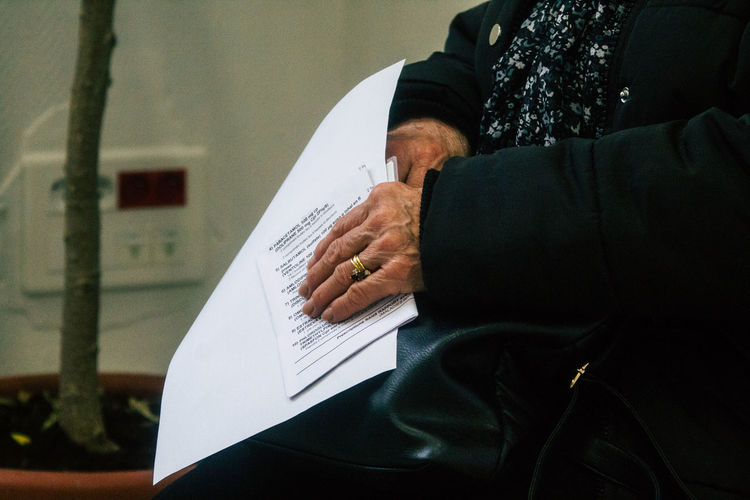 Midsection of senior woman holding documents