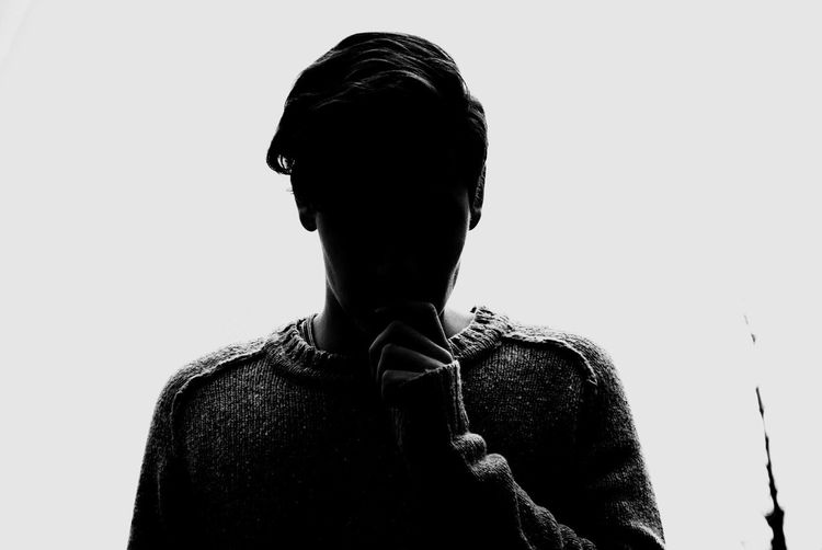Silhouette Of Person Standing Against White Background