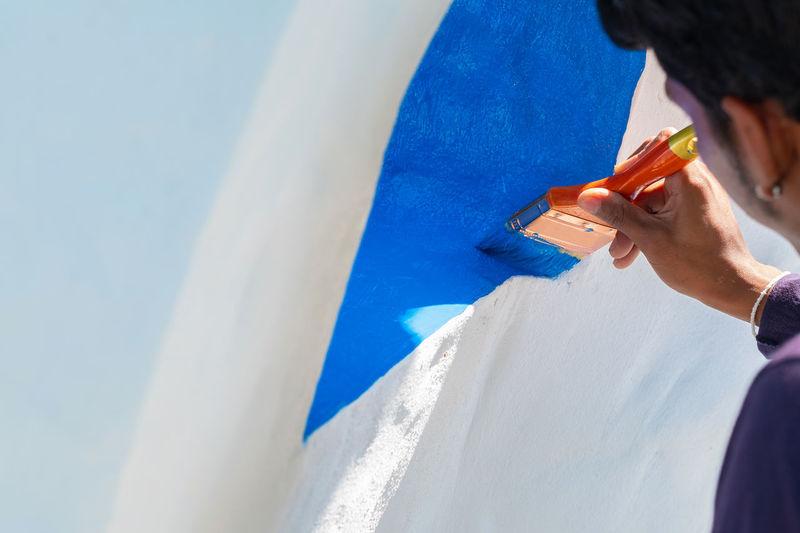 Close-up of man painting wall
