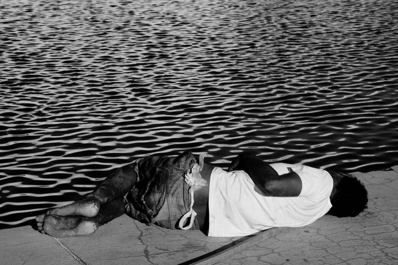 Homeless Man Sleeping By Water Pond