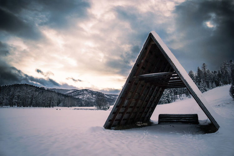 "A minimalist ""lean-to"" structure against a dramatic sky in Kalispell, Montana. Architecture Beauty In Nature Building Exterior Cloud - Sky Cold Temperature Day Mountain Nature No People Outdoors Sky Snow Winter"