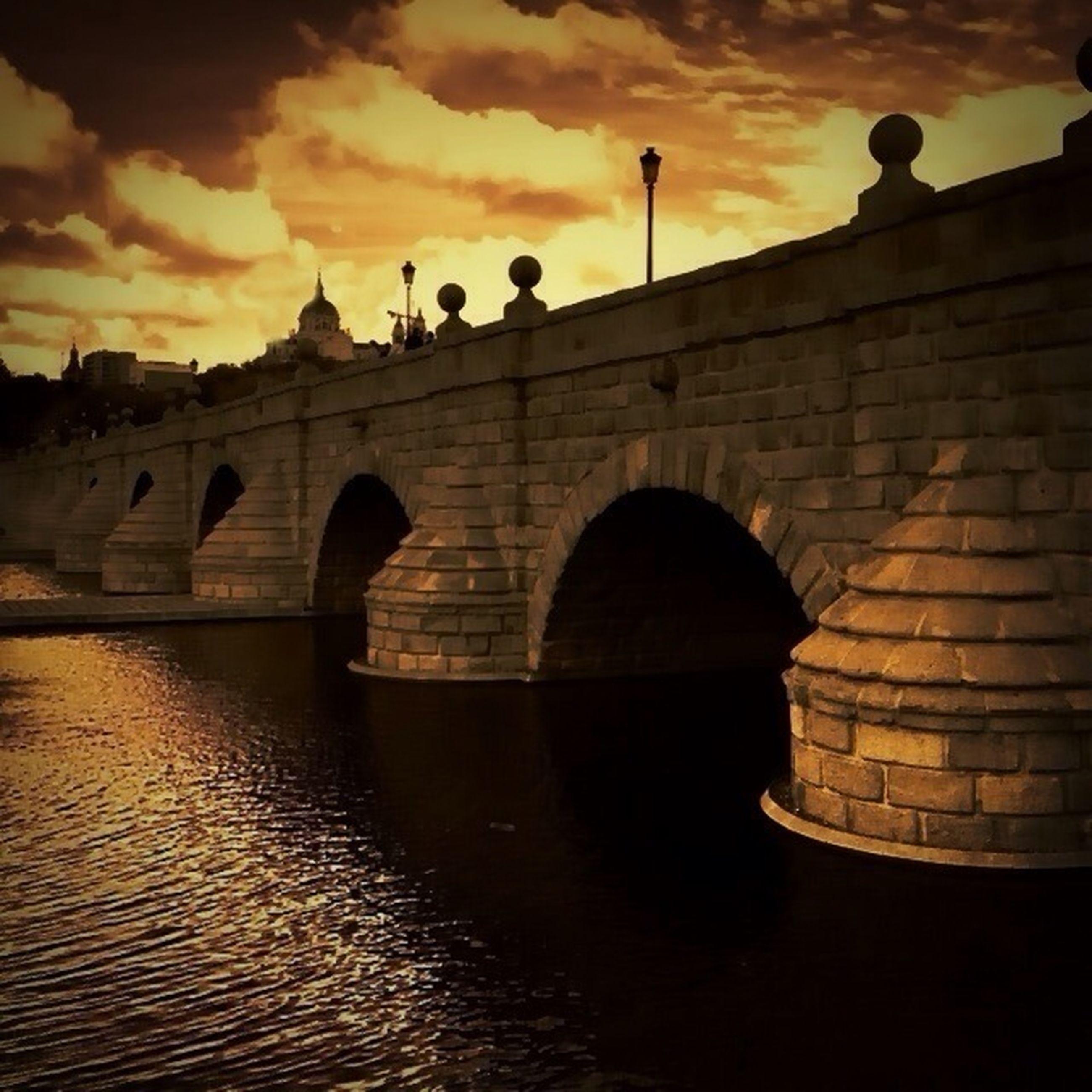 architecture, built structure, sunset, arch, sky, water, building exterior, connection, waterfront, bridge - man made structure, river, reflection, arch bridge, silhouette, cloud - sky, bridge, outdoors, orange color, dusk, no people