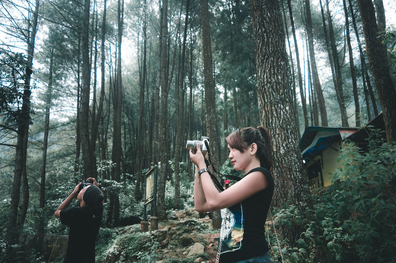 Friends photographing in forest