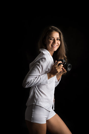 One Person Three Quarter Length Young Adult Smiling Long Hair Young Women Black Background Portrait Looking At Camera Studio Shot Beauty Hairstyle Indoors  Hair Women Beautiful Woman Standing Casual Clothing Holding