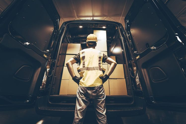 Cargo Van Delivery. Rear Cargo Doors Reloading. Construction Guy Talking Care of Fresh Supplies Delivery. Business Delivery Worker Boxes Cargo Cargo Van Delivered Hard Hat Indoors  Mode Of Transportation One Person Shipment Shipping  Truck Vehicle Vehicle Interior