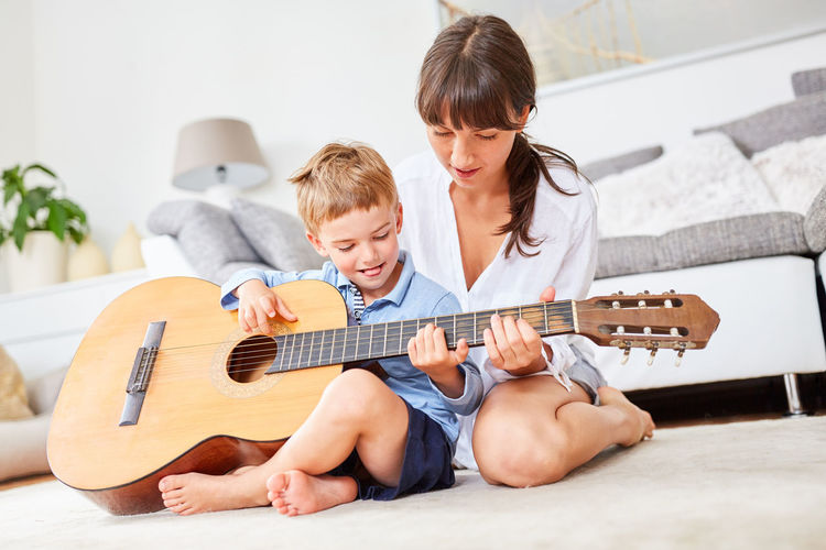Mother teaching guitar to son in living room at home