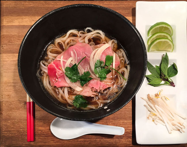 Bowl of hot Vietnamese pho noodles with garnishes Bee Beef Bowl Chopsticks Delicious Food Freshness Herb Meal Meal No People Noodles Pho Ready-to-eat Soup Spoon Still Life Table Vietnamese Vietnamese Food Wood - Material