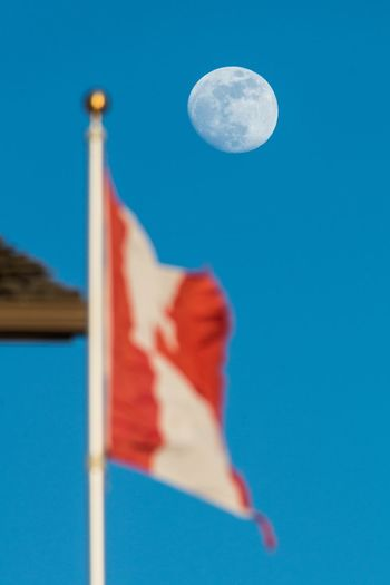 Canadian space Moon Sky Blue Flag Nature No People Full Moon Outdoors Patriotism Space Clear Sky Day Astronomy Wind Pole Environment Red